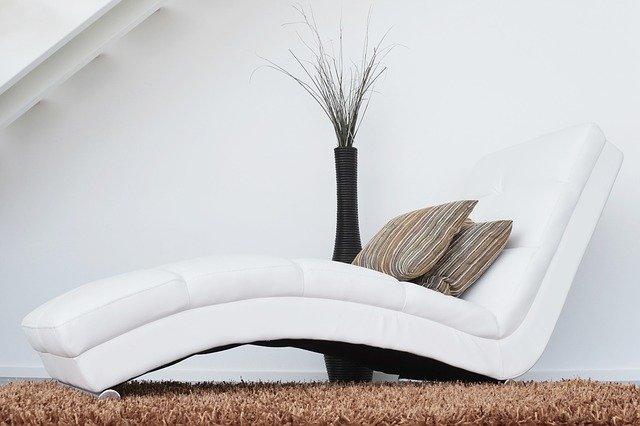 Moderná biela sedačka v netradičnom tvare s vankúšmi.jpg