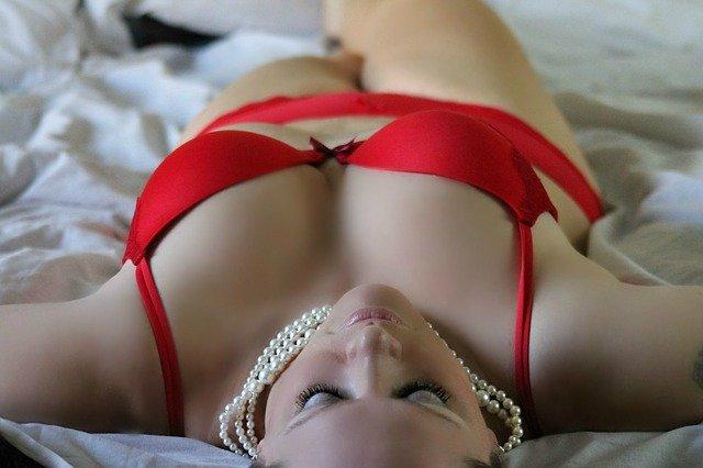 Žena v červenej podprsenke a perlovom náhrdelníku leží na posteli