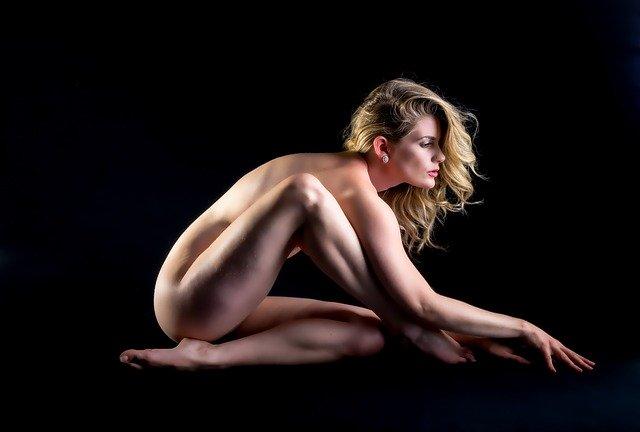 Nahá žena s blond vlasmi sedí v tme