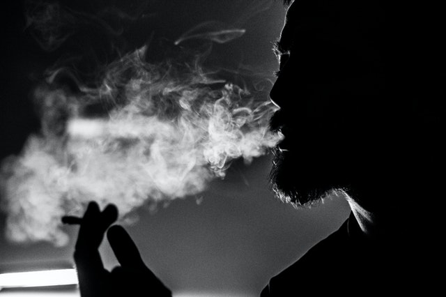 Muž fajčí cigaretu, tma