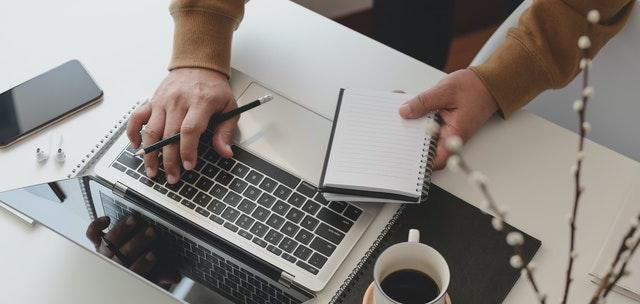 Človek píše na počítači a zapisuje si poznámky do zošita
